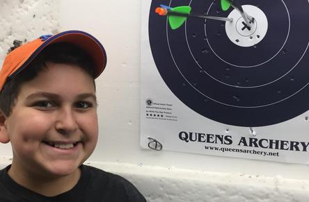 Smiling male child next to target with arrow in bullseye